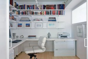 Home Office with white shelving, desk and chair